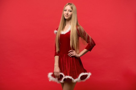 nude babe: Girl dressed as Santa on a red background Stock Photo