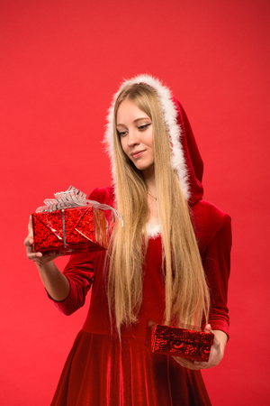 Young woman dressed as Santa holding a gift box on a red background.