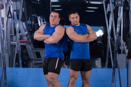 strong athletes posing in the gym on the background of mirrors