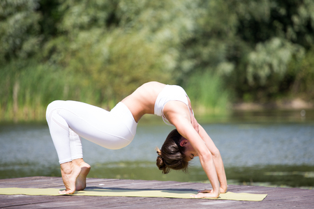 Young girl practices yoga on the shore of the lake, the concept of enjoying privacy and concentration, sunlight Banque d'images