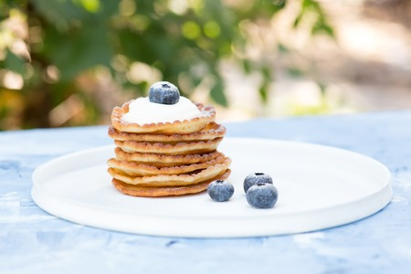 A stack of delicious pancakes with sour cream, raspberries and blueberries on a light background. with copy space. green leaves and sunlight in the background Standard-Bild