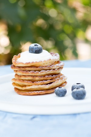 A stack of delicious pancakes with sour cream, raspberries and blueberries on a light background. with copy space