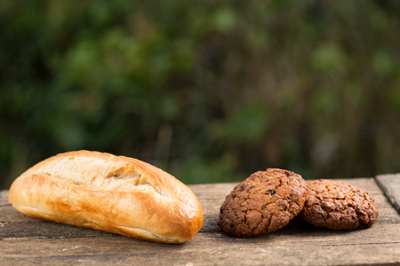 Assortment of fresh baked goods wooden background. baguette and cookies in the open space