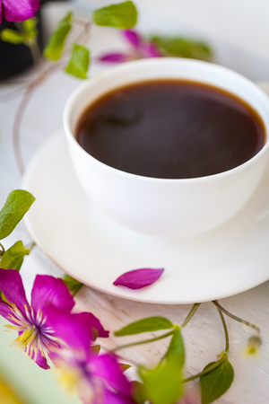 Cup of black coffee and pink blooming flowers