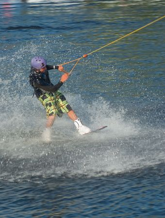 Young man wakeboarding on the lake photo