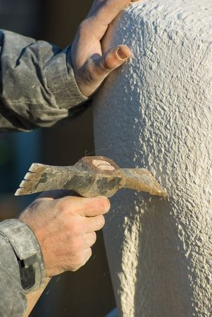Stonecutter carves with a pick sculpture of limestone