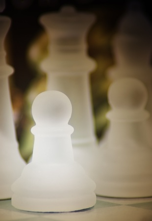 Macro shot of glass chess pawn against a dark background  photo