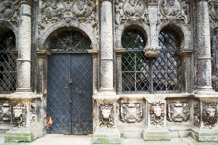 view of a wooden doorway: facade of an old church adorned with a bas-relief Stock Photo