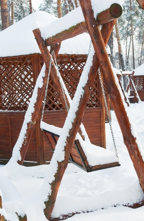 Wooden swing in a park covered with snow photo