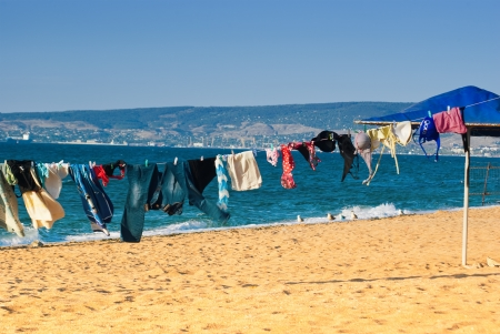 Washed clothes drying on the beach photo
