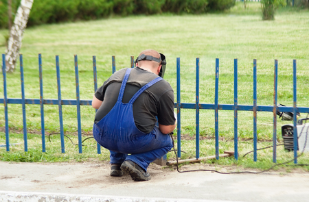 Fence installation worker welds repairing fence Standard-Bild