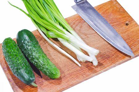 fresh cucumbers and green onions on a cutting board Standard-Bild