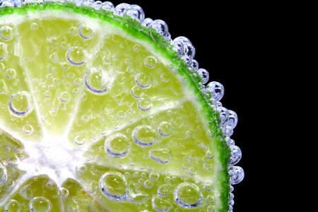 Fresh lemon slices dipped in cold water with fizzy soda. Splash it into a glass of water. Isolated on black background