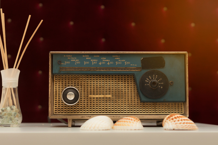 shortwave: Vintage transistor radio player on red background with sea shells Stock Photo