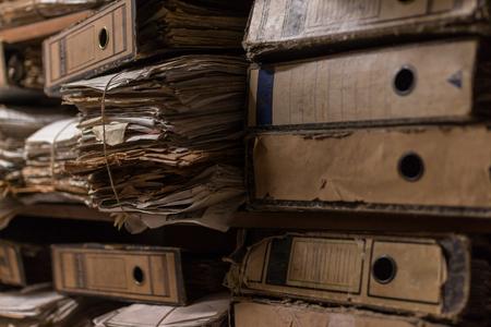 Vecchia pila polverosa di carte, file, documenti sugli scaffali della stanza dell'archivio