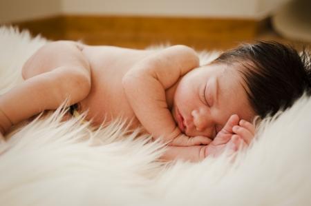 Sweeet newborn sleeping and dreaming on a hair carpet