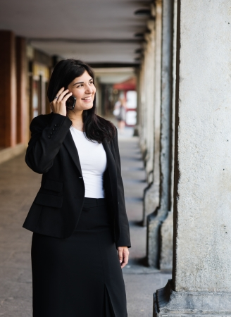 entrepeneur: Young businneswoman talking to her smartphone Stock Photo