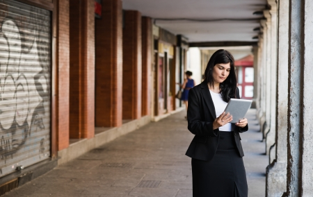entrepeneur: Brunette woman consulting her tablet Stock Photo