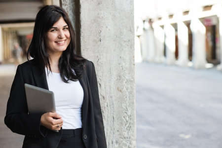 entrepeneur: Smiling brunette smiling and holding a tablet in the street