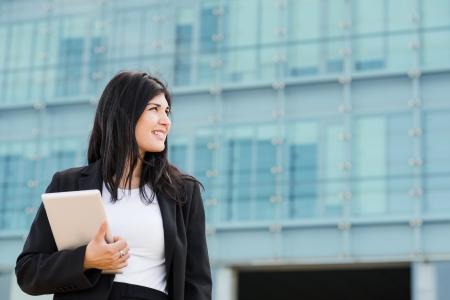 entrepeneur: Smiling brunette entrepeneur holding a tablet in front of a building