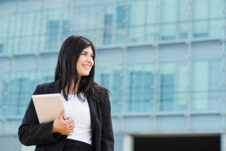 entrepeneur: Smiling brunette holding a tablet in front of a buidling Stock Photo