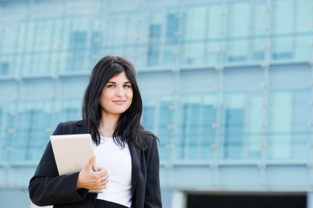 entrepeneur: YOung entrepeneur look at camera and holds a tablet in front of a building Stock Photo