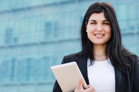 entrepeneur: PRetty entrepeneur bussineswoman holding a tablet in front of a building Stock Photo