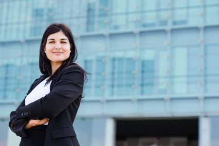 entrepeneur: Cute bussinesswoman in front of a buidling with crossed arms with copyspace to her right side Stock Photo