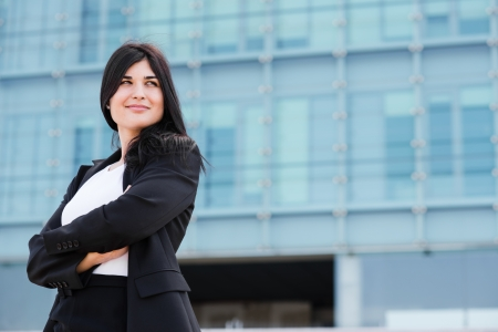 entrepeneur: Smiling brunette crossing her arms in front of a building