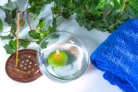 Lit candle with incense, some leaves and a blue towel, in a bathroom or a spa, with white background