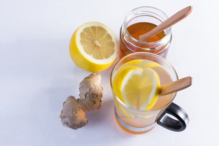 Still life of ginger infusion with ingredients, lemon and honey on a white background and on a reflecting base Reklamní fotografie