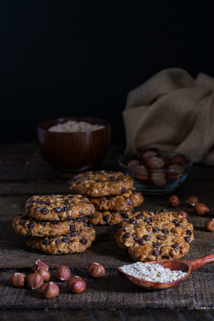 Oats cookies with chocolate chips and hazelnuts on a wood table with a bowl of oats flakes and another one of hazelnuts with shell and a cloth
