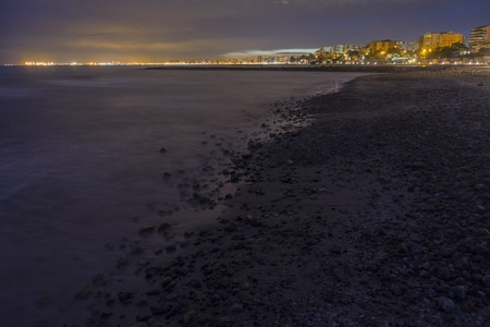 Long exposure at night on the coast with stones, looking at the buildings of Benicassim town, Castellon, Spain