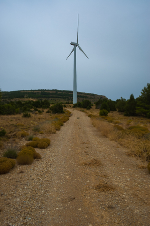 Dirt road in the countryside towards a windmill on a stormy day