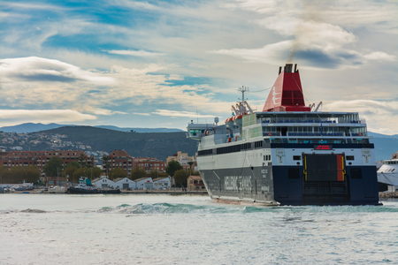 Denia, Alicante, Spain, november 21, 2018: Greek ferry arriving at the port, heading towards the dock, with the town in the background