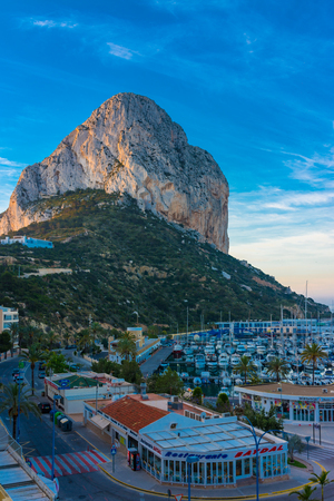 Calpe, Alicante, Spain. May 10, 2019: Rock of Ifach at sunrise. Marina, restaurants and shops