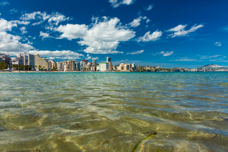 Clear crystal water at the Fossa beach, in Calpe, Alicante, Spain. Some apartment and hotel buildings