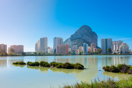 The rock of Ifach, Calpe, Alicante, Spain, next to the apartment buildings. Their reflection in the water of the saltworks