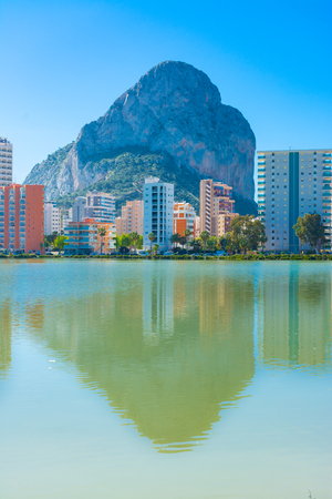 The rock of Ifach, Calpe, Alicante, Spain, and their reflection in the water of the saltworks, next to the apartment buildings