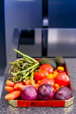 A tray of fresh vegetables and fruit, in a modern kitchen, with selective focus