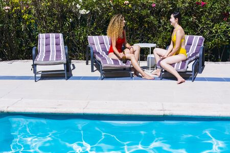 Two interracial young girls talking, drinking beer and laughing sitting on sun loungers by a pool