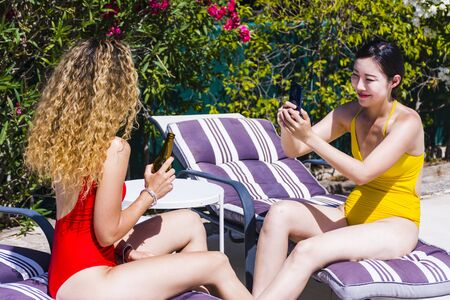 Two interracial young girls taking pictures of each other with mobile phone, having fun and drinking beer sitting on sun loungers by a pool