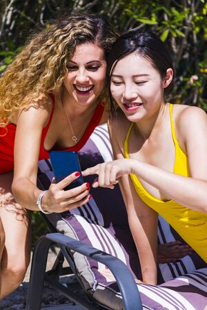 Two interracial young girls watching pictures together on the mobile phone, having fun and drinking beer sitting on sun loungers by a pool