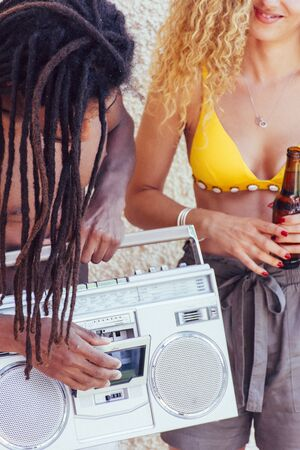 Interracial couple having fun, drinking beer and listening to music from an old device. Party and fun concept 版權商用圖片