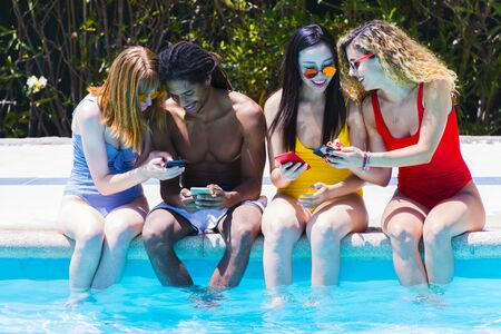 Four interracial young people sitting on the edge of the pool having fun checking their mobile phones Stock fotó