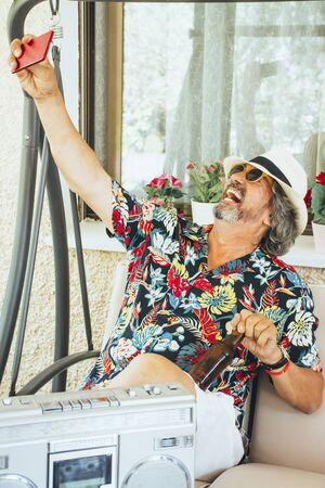 Mature man enjoying taking selfies with mobile phone while sitting on a swing chair, with a beer and listening music from a radio cassette player 版權商用圖片