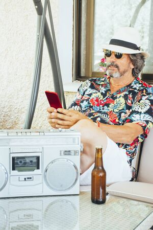 Mature man looking at his mobile phone while sitting on a swing chair, with a beer and listening music from a radio cassette player 版權商用圖片