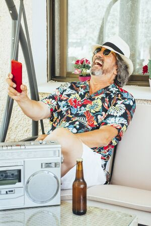 Mature man having fun with his mobile phone while sitting on a swing chair with a beer and listening music from a radio cassette player