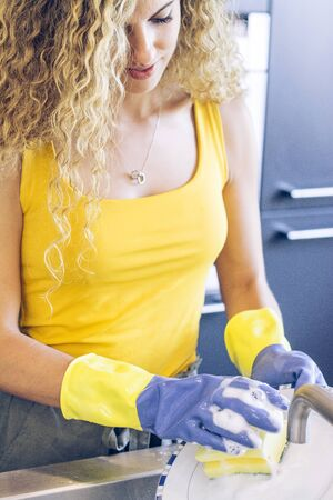 Young, blonde and smiling girl scrubbing a plate in the kitchen sink with blue and yellow rubber gloves