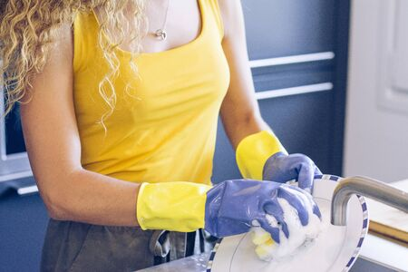 Young blonde girl scrubbing a plate in the kitchen sink with blue and yellow rubber gloves Stock fotó